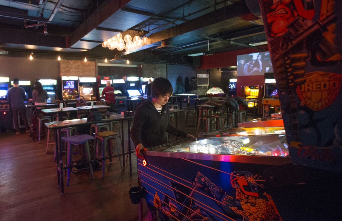 Tilt Game Bar with rows of pinball and retro arcade machines line up the walls with bar tables in the middle